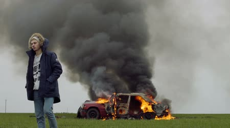 The guy walks away from the burning red car, car crash
