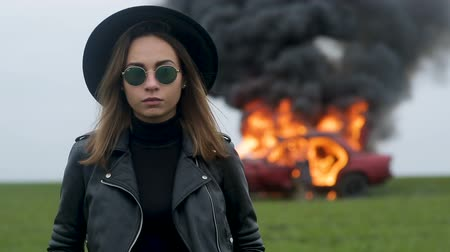 Girl musician on the background of a burning car, a stern look, a girl in black, a car explosion