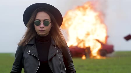 feminist : Stylish model against the background of an exploding car, girl and exploding car