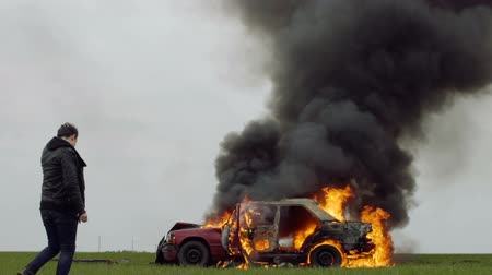 A sad man at a burning car, sadness and sadness, a fire, a guy expects firefighters Stok Video