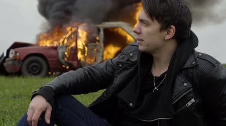 Survivor in a car crash a man sits near a burning car, a guy sits on the background of a burning car Stok Video