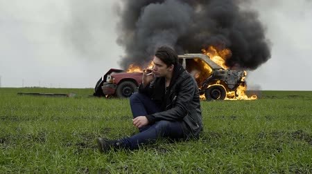 A guy lights a cigarette against the backdrop of his burning car, the harm of smoking, a man smokes against the background of a fire car, slow-mo