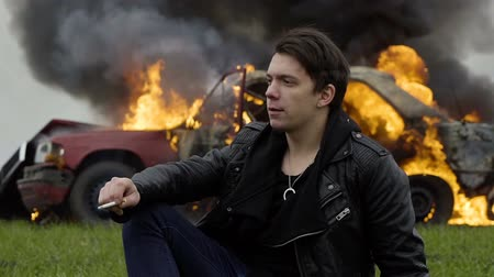 Man smokes against the background of a burning car, despair, a fire, an explosion of a car Stok Video