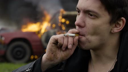 resistência : The thoughtful guy smokes against the background of his burning car, melancholy, an explosion of a car