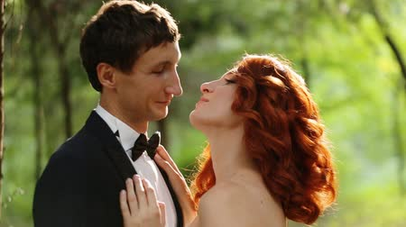 smokin : redhead bride and groom embracing in forest