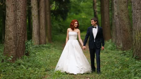 redhead suit : bride and groom holding hands go through forest