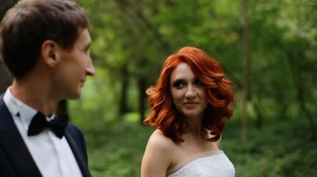 redhead suit : bride and groom look at each other
