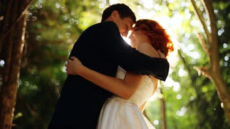 redhead suit : bride and groom embracing in sunlight