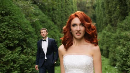 redhead suit : and groom are among fir trees closeup