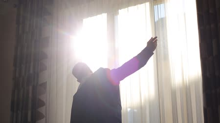 iyi giyimli : Silhouette of a man putting on his jacket before the wedding