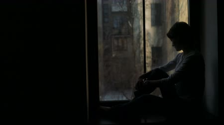 devanear : Silhouette of sad woman sitting on the sill and looking out the window