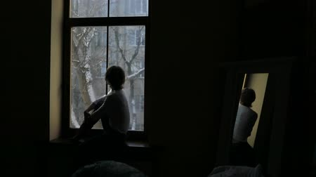 představit si : Silhouette of a woman sitting on the sill and looking out the window Dostupné videozáznamy