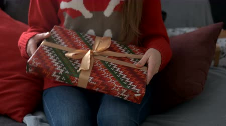 конверт : Attractive happy woman holding and huging a gift on sofa on christmas tree background.