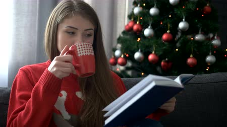 sock : Portrait of beautiful woman wearing stylish sweater and reading a book sitting on comfortable sofa enjoying hot drink.