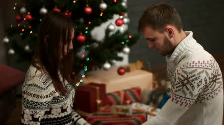 dát : Beatiful young couple opening the christmas presents siting on the floor near christmastree with bokeh from light. Dostupné videozáznamy