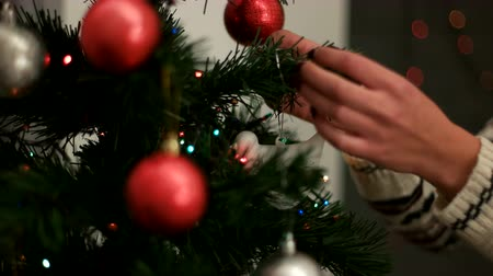 вешать : Woman hands decorating a Christmas tree red and silver toys in living room. Close up.