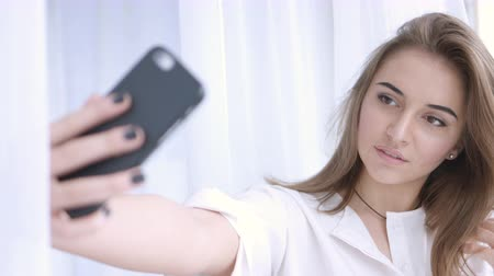 self portrait photography : Young brunette girl takes photograph of herself on mobile phone, a selfie Stock Footage