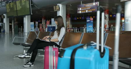 lounge : Young attractive brunette using laptop in lounge zone for chatting with friend while waiting here flight it the international airport.