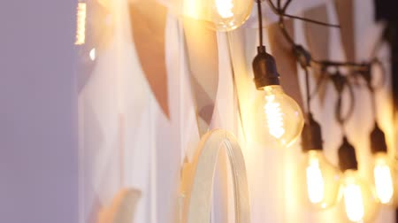 getting electricity : Close up shot of light bulbs garland on the white wall.