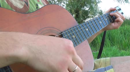 plucks : Man Elegant Plucks the Strings, Playing Guitar on Natural Background. Stock Footage