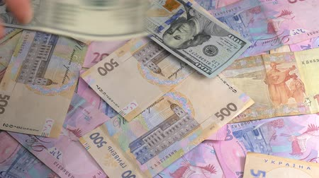 filigran : Old and new money dollar and hryvnia is falling on the table.