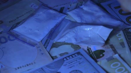 crystalmeth : Drugs and cash money everywhere on a table. Closeup shot. Ultraviolet light Stock Footage