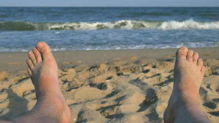 bare foot : Man feet sunbathing on the beach against the background of sand and blue sea with waves, Man bare feet on a beach