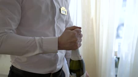 champagne bottles : Waiter uncorking a bottle of champagne