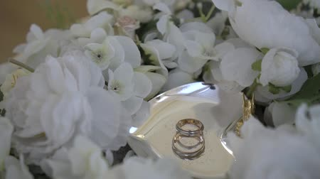 bouquets : Gold wedding rings on a metal saucer surrounded by bouquet of white roses Stock Footage