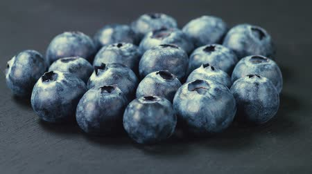 picked up : A pile of blueberry or huckleberries on a black background turning in front of the camera. The motion is loopable. Close up shot. Stock Footage