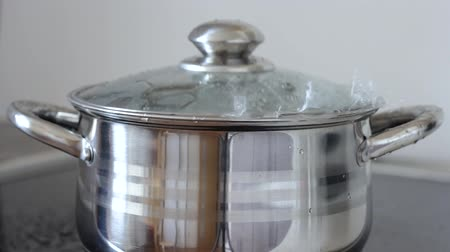 panelas : Boiling water in a saucepan with glass lid. Water gurgles, sprinkles and flows from pan.