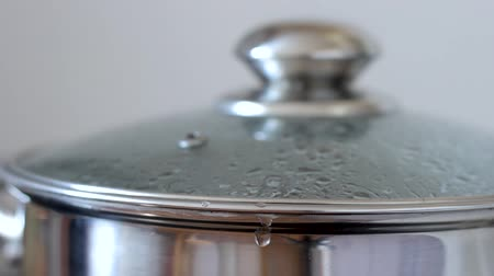 lids : Boiling water in a saucepan with glass lid, closeup. Water gurgles, sprinkles and flows from pan.