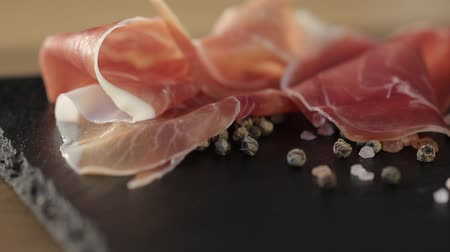 italian speciality : Thin slices of pork ham on the wood plate. Dolly shot. Closeup