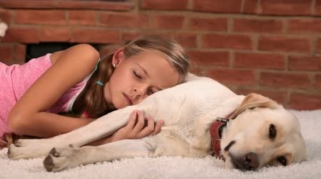 animais e animais de estimação : Girl relaxing with her labrador dog lying on the carpet - closeup