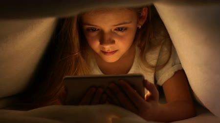 cover : Young girl watching online content on her smartphone at night - hiding under the blanket, static camera