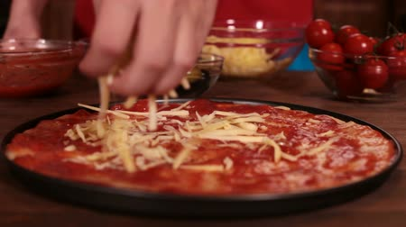 refocus : Phases of making a pizza - putting on the grated cheese, closeup, rack focus Stock Footage