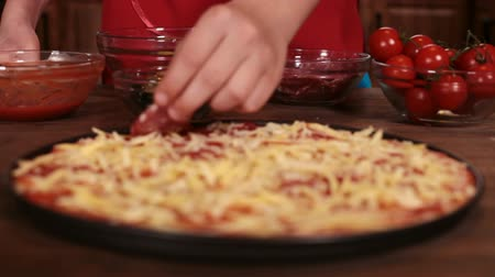 refocus : Phases of making a pizza - putting on the salami slices, closeup, rack focus Stock Footage