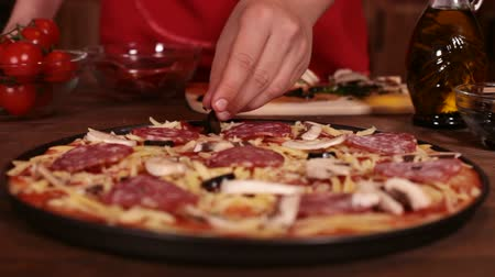 refocus : Phases of making a pizza - putting on the sliced olives, closeup, rack focus