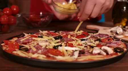refocus : Phases of making a pizza - finishing touches with some extra cheese, closeup, rack focus