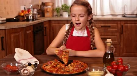 voracious : Young girl about to taste some home made pizza, smiling with anticipation