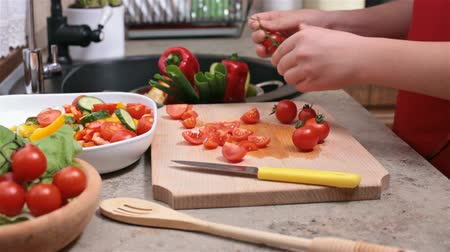 разделочная доска : Child hands preparing tomatos for a vegetables salad - side view  of the cutting board at the kitchen sink