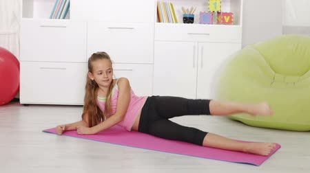 gimnastyka : Young girl exercising at home - lying on exercise mat Wideo