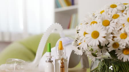 refocus : Functioning nebuliser inhaler device revealing from behind daisy bouquet, allergy concept - rack focus, camera dolly