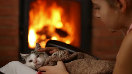Young girl with rescue kitten at the fireplace - providing warmth, comfort and a new home, closeup