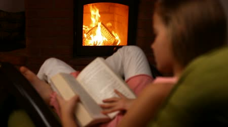 refocus : Young girl reading a book sitting in a rocking chair by the fire in the dark room - camera moves toward the fire, refocusing