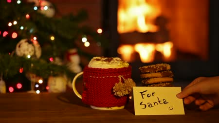 czekolada : Cookies and hot chocolate prepared for santa - hand placing card in front of fireplace and christmas tree