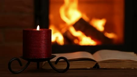 Reading an old book at the fireplace in the evening - hand turning page