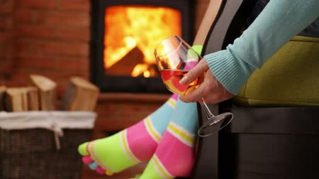 happy socks : Woman feet hanging on rocking chair, swinging in front of fireplace, hand holding a glass of wine - relaxing concept, static camera, closeup