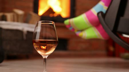 Woman feet hanging on rocking chair, swinging in front of fireplace with a glass of wine nearby - relaxing concept, static camera, closeup Stock Footage