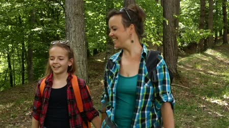 Hikers enjoy walking in summer forest - woman and girl walking downhill among trees